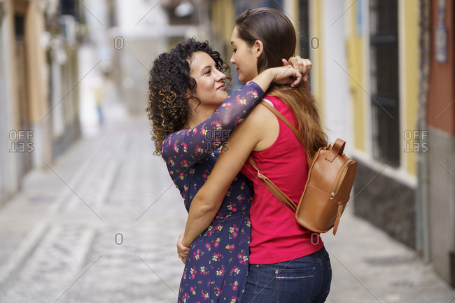 Romantic couple embracing each other while standing on footpath in city