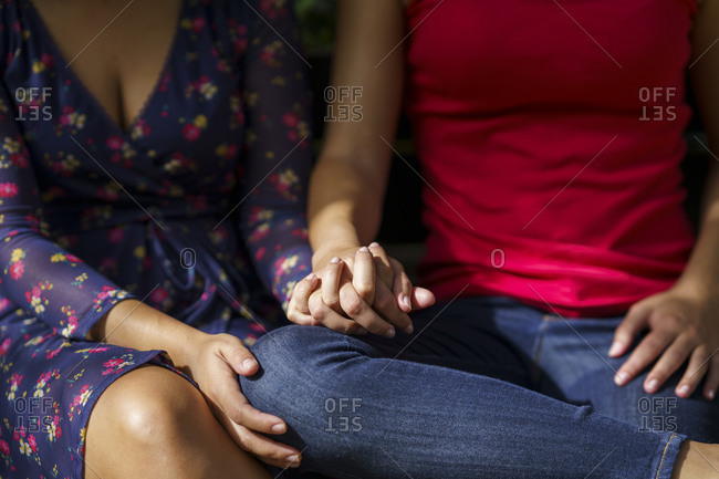 Lesbian couple sitting with hands clasped at public park