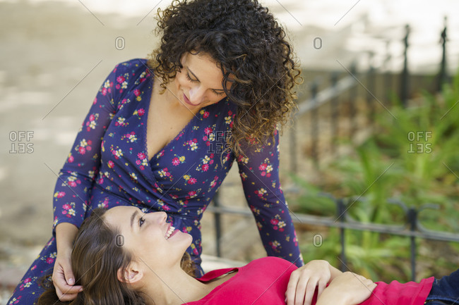 Smiling girlfriend lying on woman lap at public park