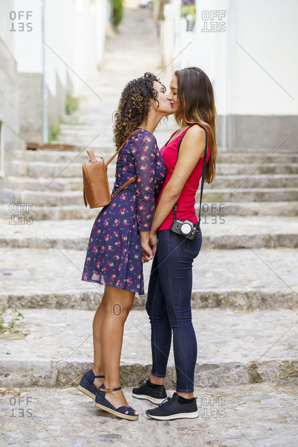 Lesbian couple kissing while standing against staircase in city