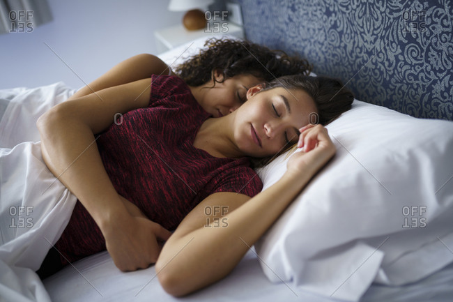 Beautiful lesbian couple sleeping on bed at home