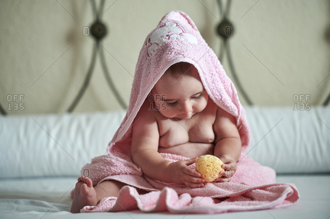 Baby girl in pink towel playing with bath sponge on bed at home