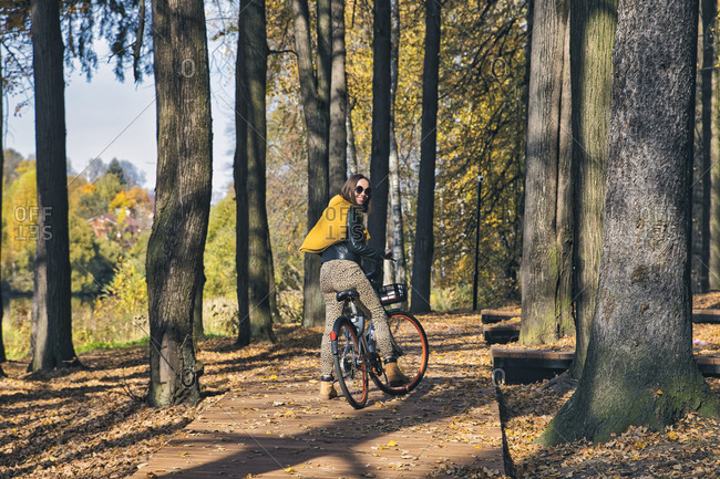 Woman looking over shoulder while riding bicycle in public park