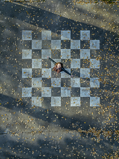 Mid adult woman with arms outstretched spinning on asphalt painted with chessboard pattern