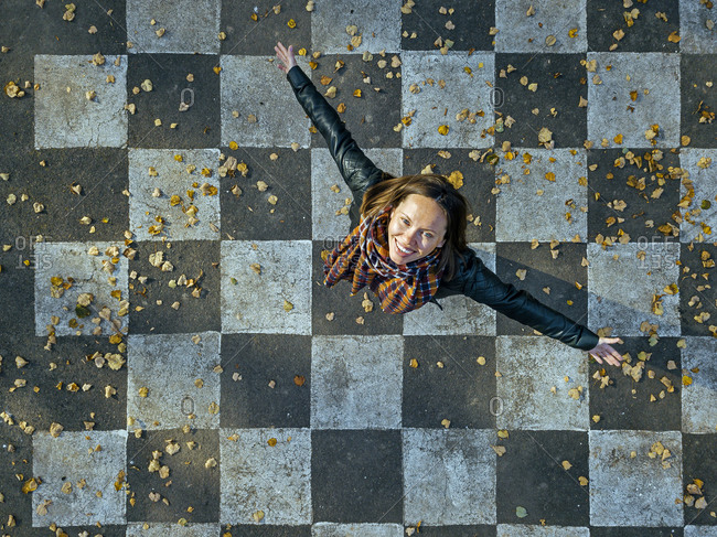 Smiling woman with arms outstretched spinning on asphalt painted with checked pattern