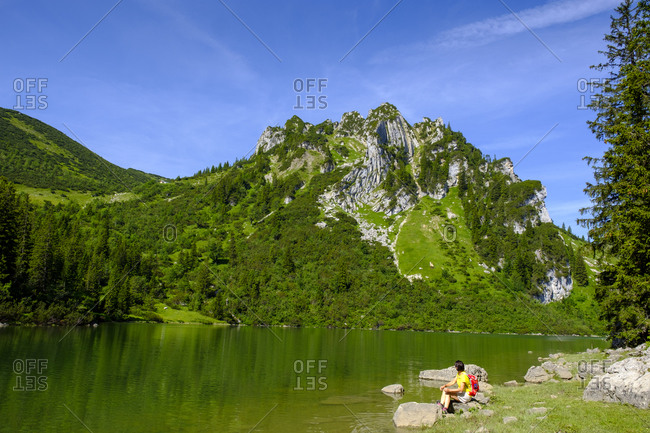 Female hiker resting on green shore of Soinsee lake with Ruchenkopfe mountain in background