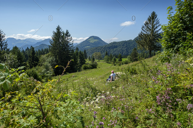 Senior woman relaxing in alpine meadow during summer
