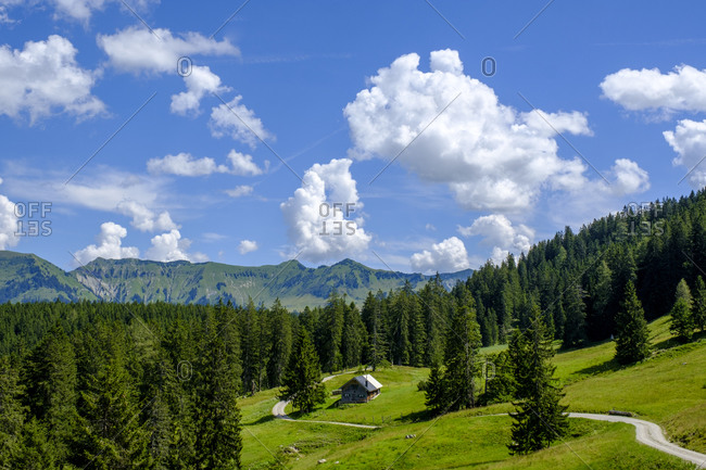 Scenic view of clouds over lone hut in Bavarian Alps during summer