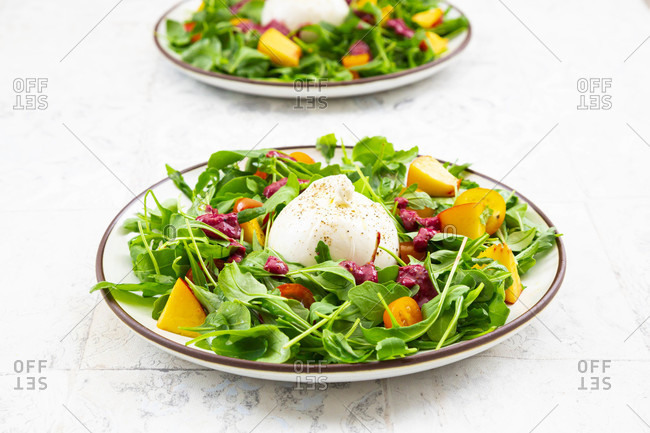 Two plates of vegetarian salad with fruits- vegetables and burrata cheese