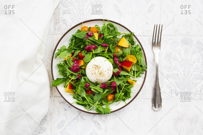 Plate of vegetarian salad with fruits- vegetables and burrata cheese