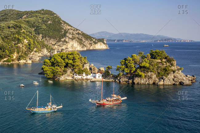 Greece- Preveza- Parga- Ships sailing in front of Panagia Chapel in summer