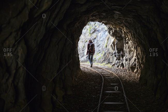 Male hiker walking through tunnel on Tracciolino trail
