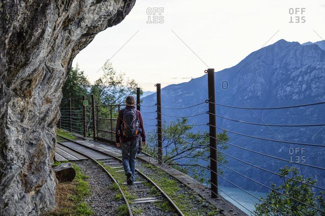 Man hiking alongTracciolinorailroad track at dusk