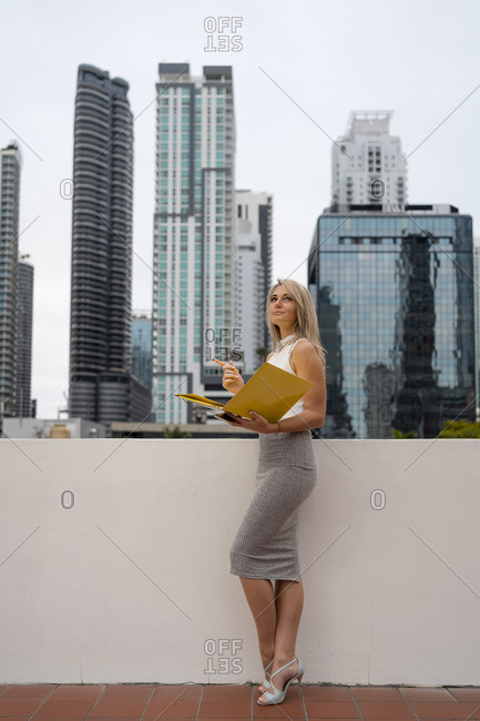 Beautiful businesswoman looking away while holding file against modern skyscrapers at downtown