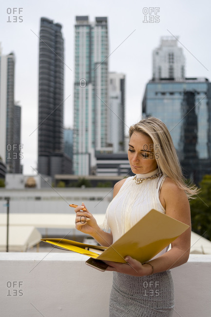 Blond female professional analyzing document in file while standing against skyscrapers at downtown
