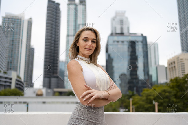 Confident beautiful female entrepreneur standing with arms crossed against tall modern skyscrapers at downtown in city