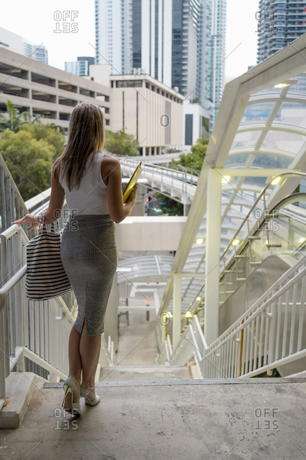 Female entrepreneur moving down staircase at downtown in city