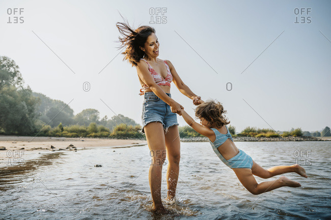 Mother whirling daughter around while standing in water at beach