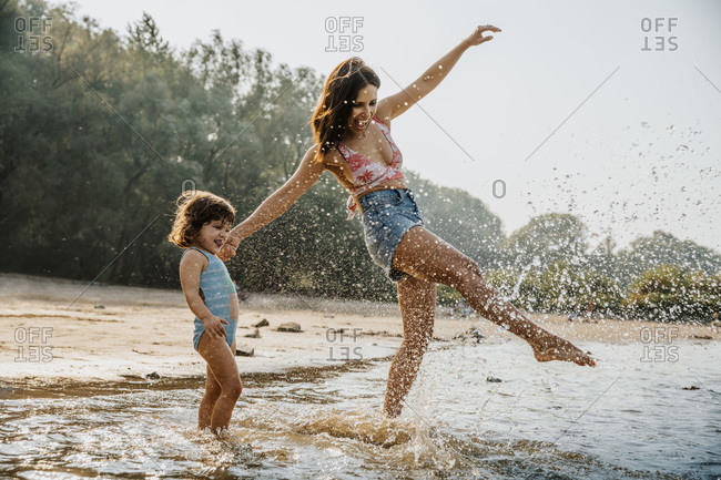 Mother and daughter enjoying in water at beach