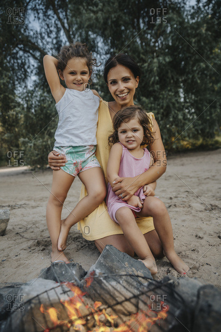 Daughters and mother sitting in front of campfire at beach