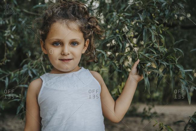 Cute little girl standing under willow tree