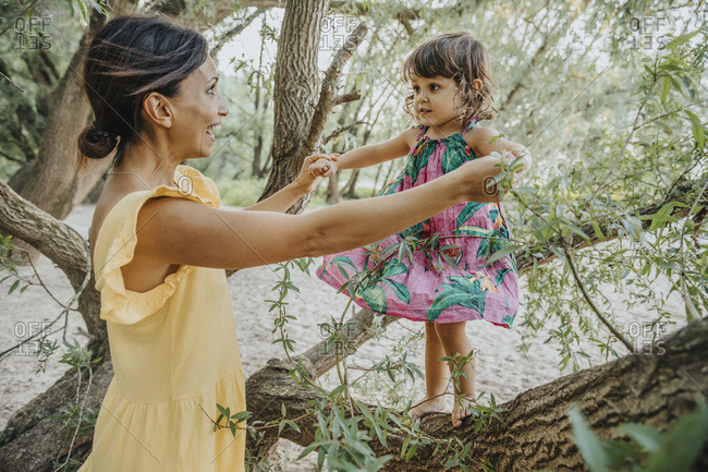 Mother helping daughter to stand on will tree branch
