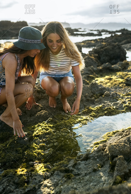 Cheerful young women crouching by puddle on rock while enjoying weekend at beach