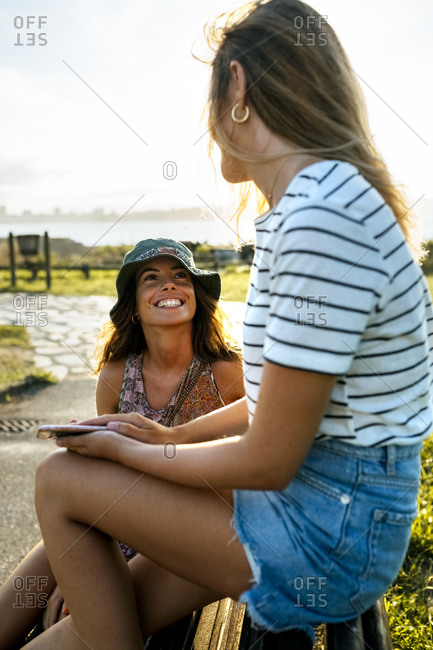Smiling young women talking while spending weekend together
