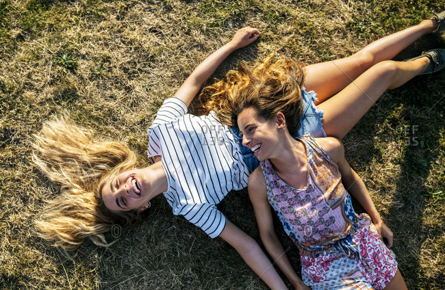 Happy young female friends relaxing on field during weekend
