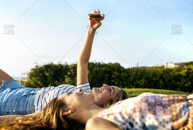 Smiling young woman taking selfie with female friend while relaxing on field during sunny day