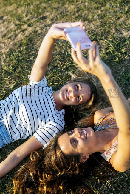 Happy young women taking selfie while relaxing on field during sunny day