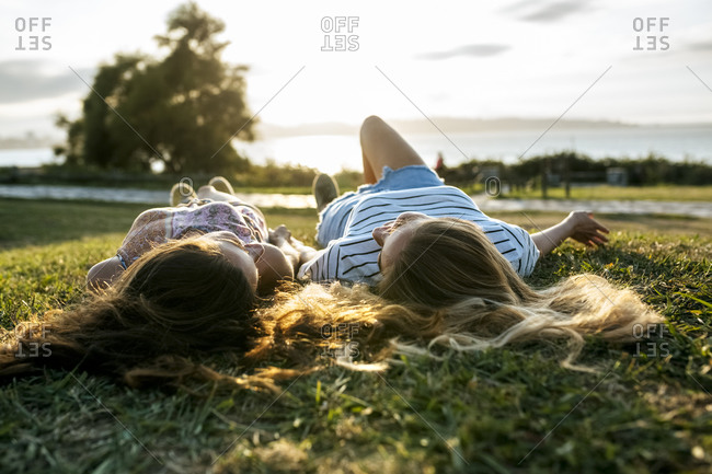 Young female friends relaxing on field while spending weekend together