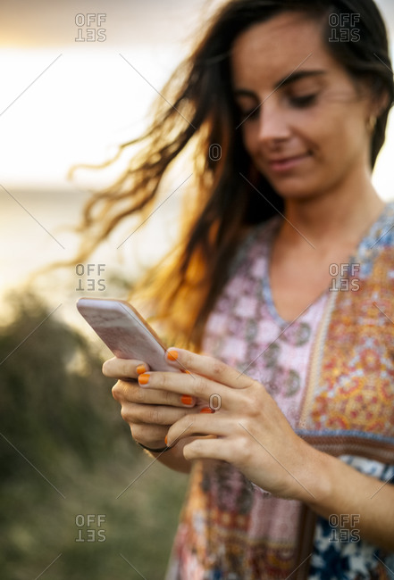 Young woman using smart phone on field during sunset