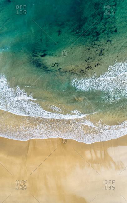 Aerial view of edge of sandy coastal beach