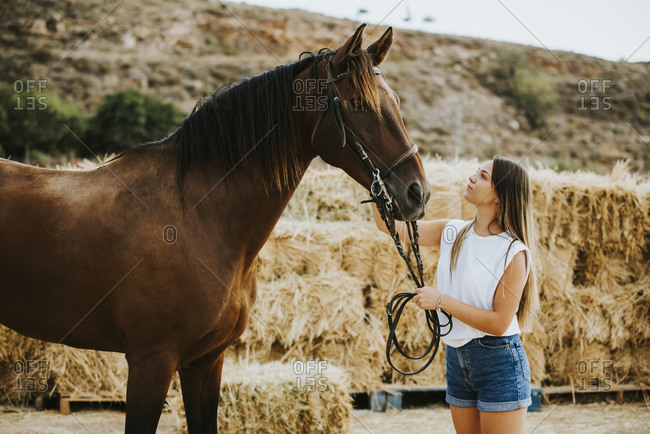 Beautiful young woman holding reins of brown horse