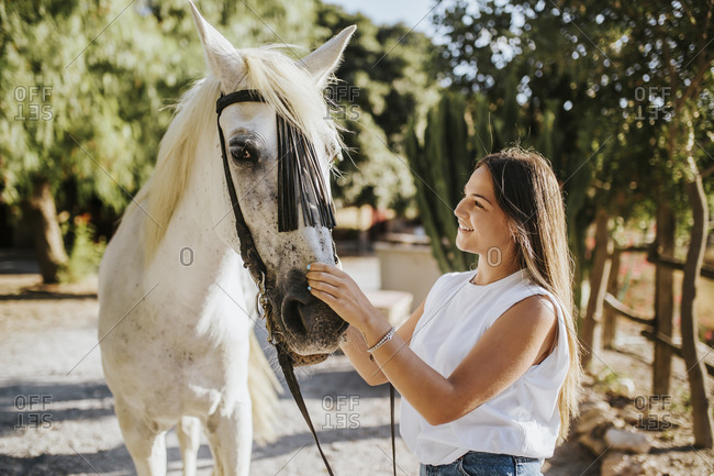 Beautiful young woman gently stroking white horse