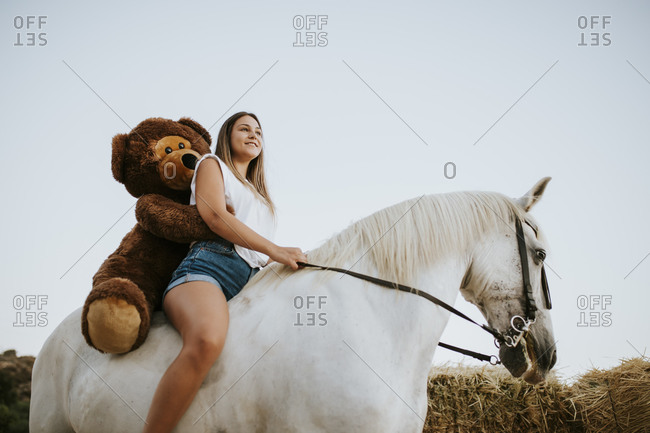 Beautiful young woman riding horse with large teddy bear behind