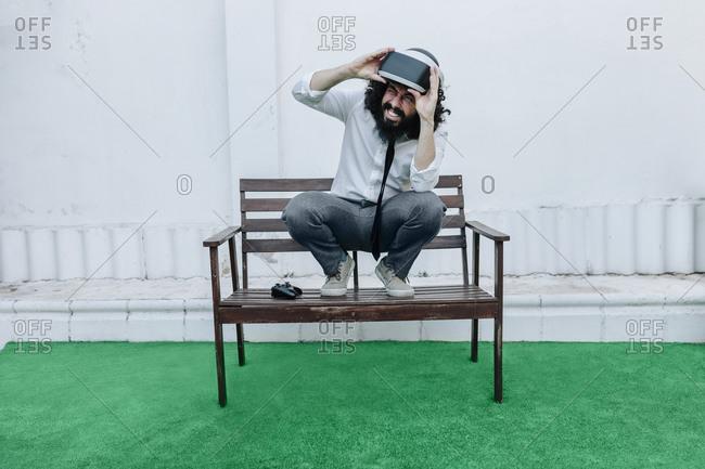 Man removing virtual reality eyeglasses while crouching on bench at backyard