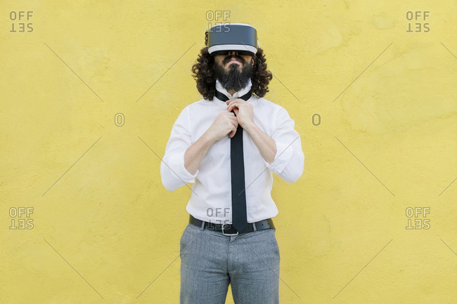 Businessman wearing virtual reality eyeglasses tying tie while standing against yellow wall