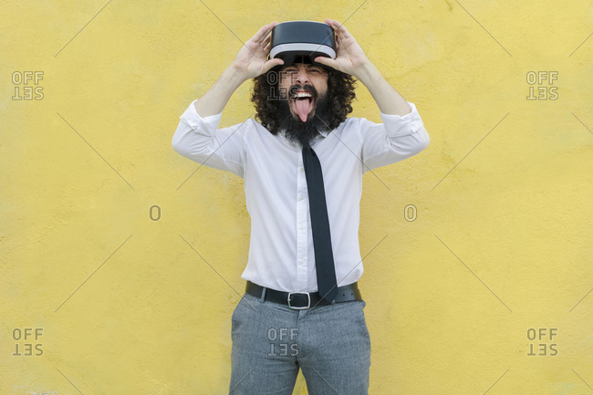 Man teasing with sticking out tongue while removing virtual reality glasses against wall