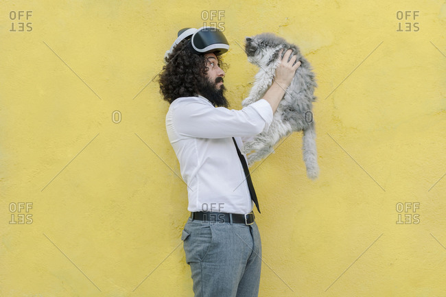 Man with virtual reality eyeglasses on head playing with cat while standing against wall