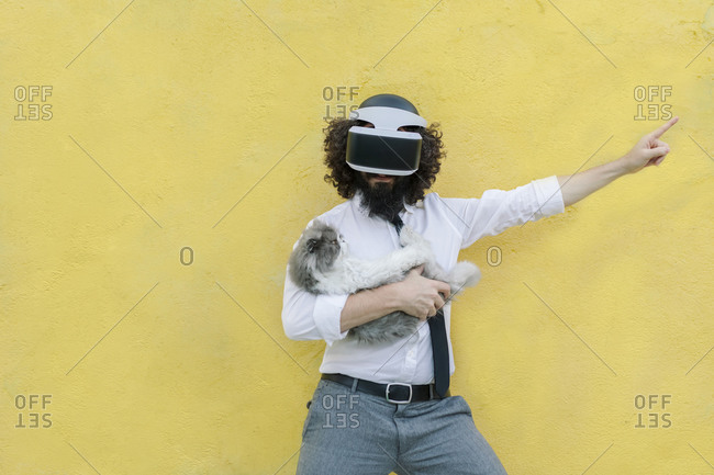 Man wearing virtual reality eyeglasses holding cat while standing against wall