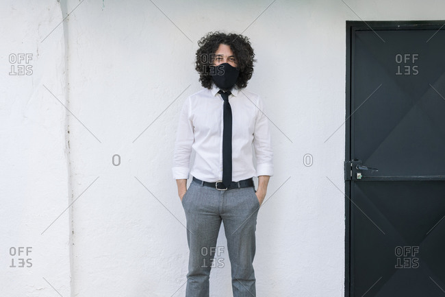 Businessman with protective face mask and hands in pockets standing against wall