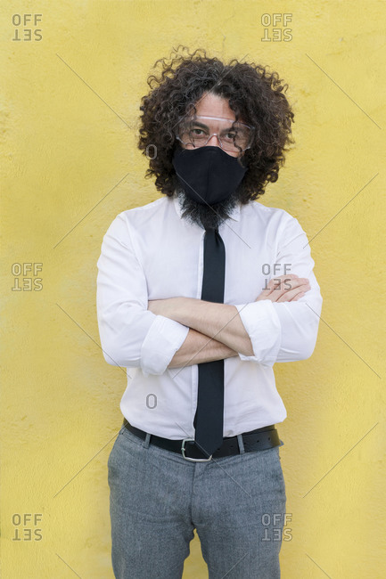 Businessman wearing face mask and eyeglasses standing with arms crossed against wall