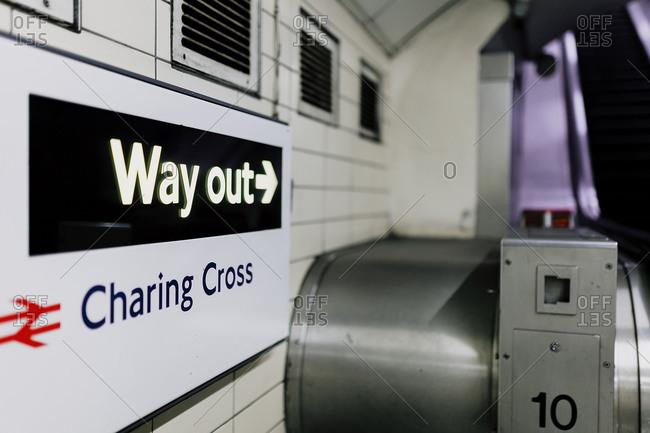 UK- England- London- Directional sign over turnstile in railroad station