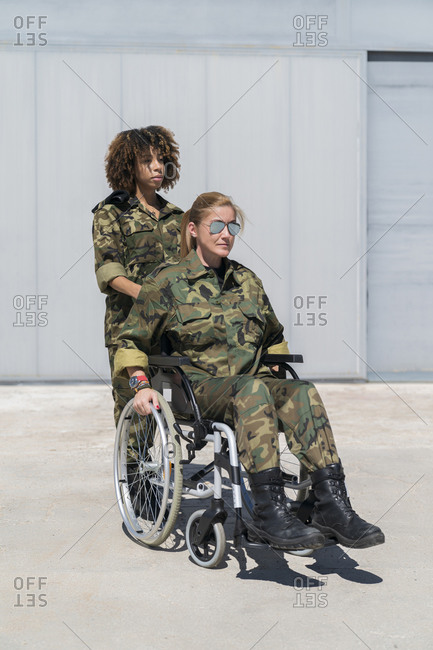Young female military soldier pushing colleague on wheelchair at army base during sunny day