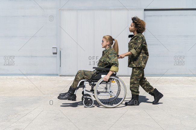 Young female military soldier pushing mature colleague on wheelchair at army base during sunny day