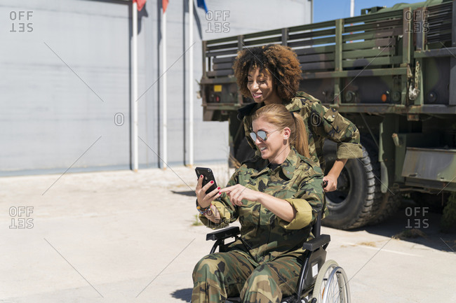 Smiling disabled female soldier taking selfie with young colleague against truck at army base on sunny day