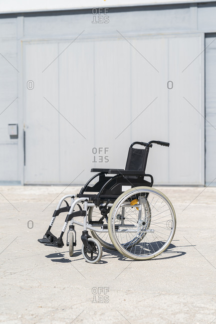 Empty wheelchair at military base on sunny day