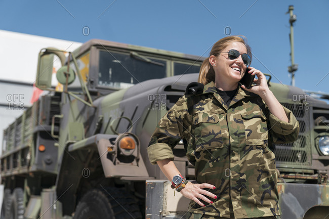 Smiling mature female army soldier talking on mobile phone while standing against truck at base on sunny day